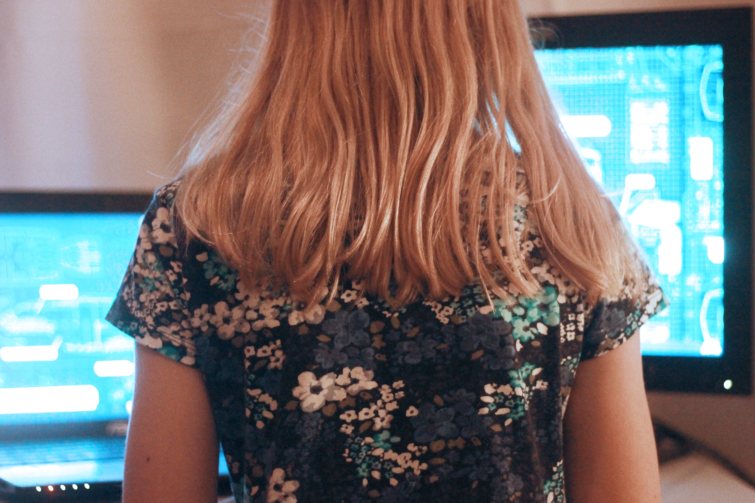 girl standing in front of computer screens