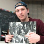 student holding photo of potsdam conference